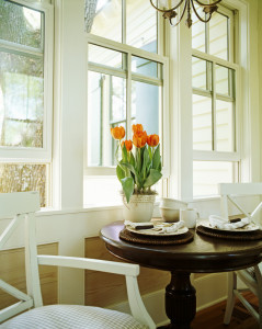 Flower pot bearing orange flowers is kept on the round table near the window --- Image by © Royalty-Free/Corbis